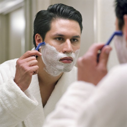 Stock Photo: 1598R-16396 Man in robe shaving, reflecting in bathroom mirror