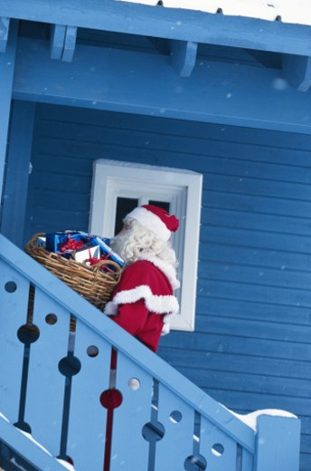 Stock Photo: 1598R-167460 Santa Claus on stairs of house with gifts