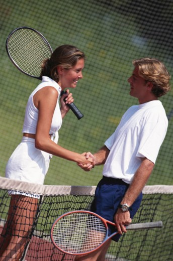 Couple shaking hands on  tennis court : Stock Photo