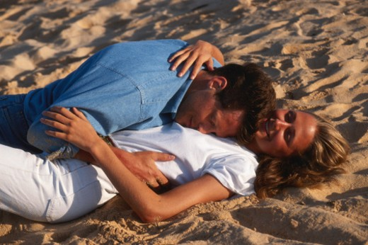 Couple embracing at sandy beach : Stock Photo