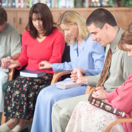 Group of women and men praying, holding hands : Stock Photo