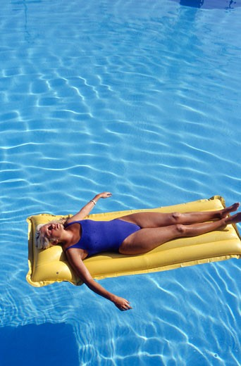 Stock Photo: 1598R-168369 Young woman on air bed in pool, elevated view