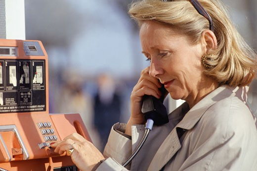 Mature woman dialling number on pay phone, side view : Stock Photo