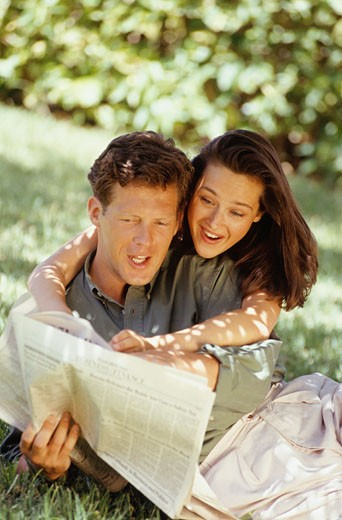 Couple lying on grass, reading newspaper : Stock Photo