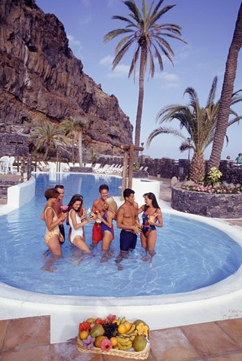 Group standing with exotic cocktails in pool, elevated view : Stock Photo