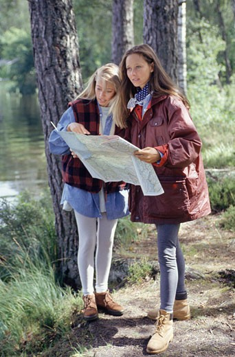 Stock Photo: 1598R-169851 Two women reading map in forest