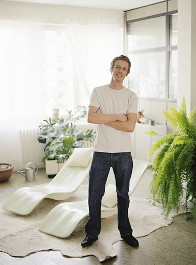 Young man standing in conservatory, arms folded, portrait : Stock Photo