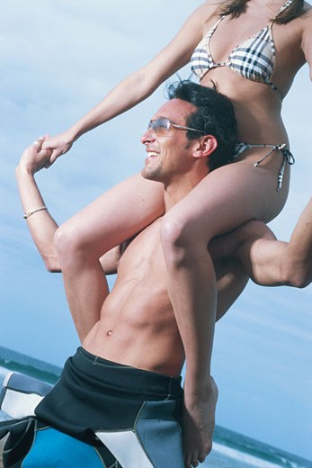 Young woman sitting on man's shoulders : Stock Photo