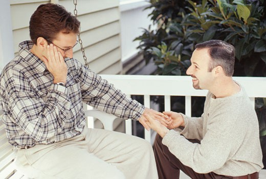 Man putting wedding ring on finger of man : Stock Photo