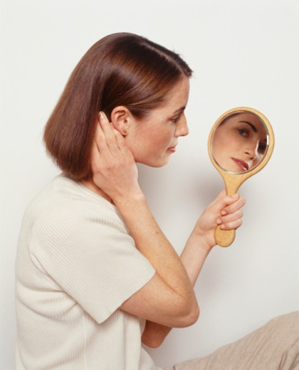 Young woman looking in mirror, side view : Stock Photo