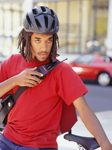 Courier on bike using walkie talkie : Stock Photo