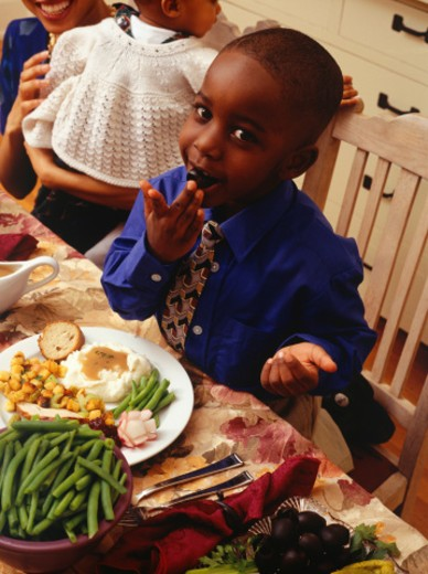 Stock Photo: 1598R-172632 Boy (6-7) putting olive in mouth at Thanksgiving dinner