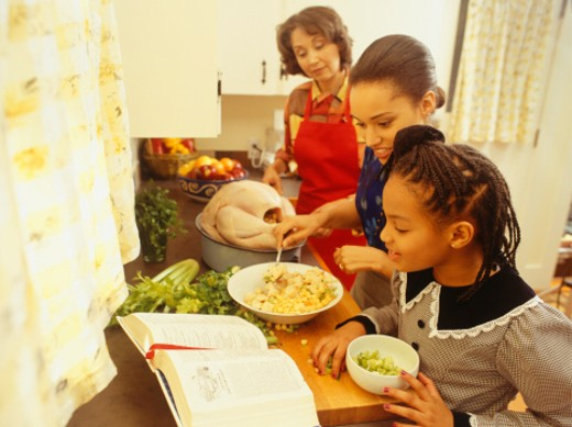 Mother helping daughters prepare food in kitchen : Stock Photo