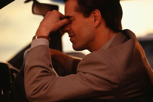 Troubled businessman in car : Stock Photo