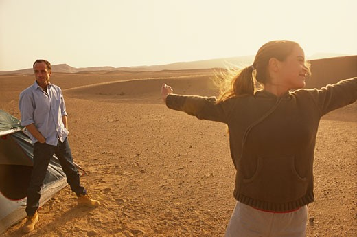 Couple at desert, woman standing with arms outstretched : Stock Photo