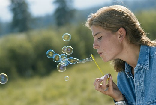 Stock Photo: 1598R-173679 Young woman blowing bubbles