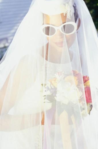 Stock Photo: 1598R-174987 Bride wearing sunglasses under veil, outdoors, portrait