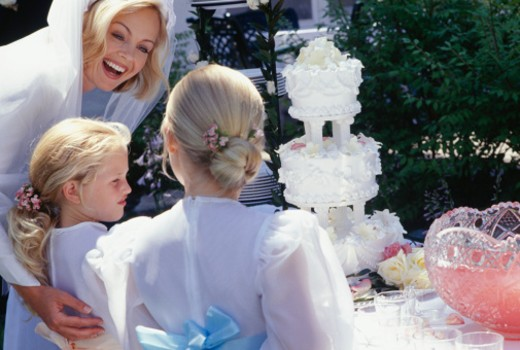 Bride and flower girls (12-13) (13-14) with wedding cake : Stock Photo