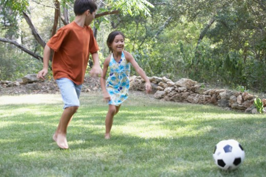 Stock Photo: 1598R-175711 Front profile of a boy and a girl playing football in a garden