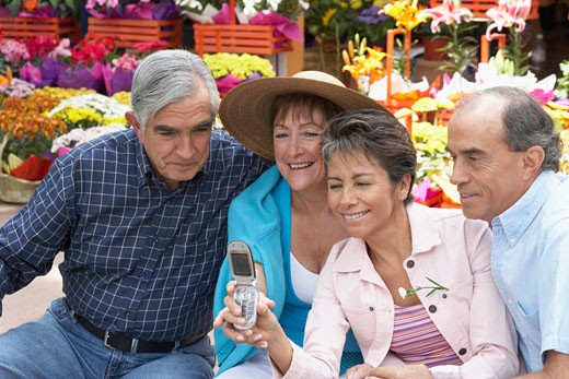 Stock Photo: 1598R-176199 Two mature couples looking at the screen of a mobile phone