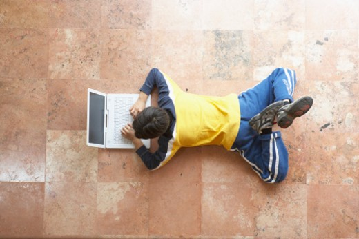 High angle view of a boy lying on the floor and working on a laptop : Stock Photo