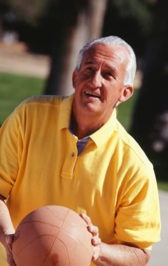 Stock Photo: 1598R-176285 Senior man preparing to shoot basketball, outdoors