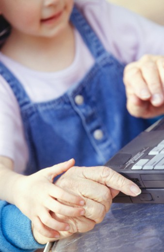 Grandfather and granddaughter (4-5) using laptop, close up of hands : Stock Photo
