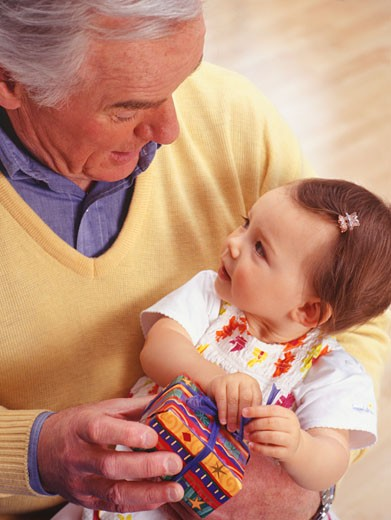Stock Photo: 1598R-176816 Grandfather holding baby girl (12-18 months), indoors, elevated view