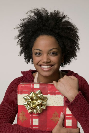 Woman with frizzy hair clutching large gift : Stock Photo