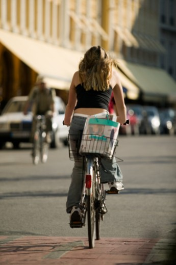 Young woman cycling on city street, rear view : Stock Photo