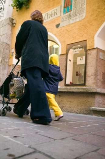 Stock Photo: 1598R-177746 Mother pushing pram down city street, walking beside other young child (4-5), low angle view