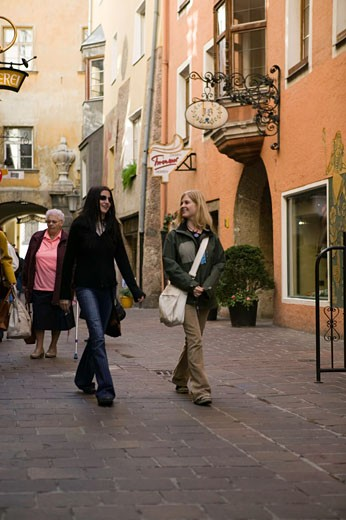 Two women walking down street of old historical city : Stock Photo