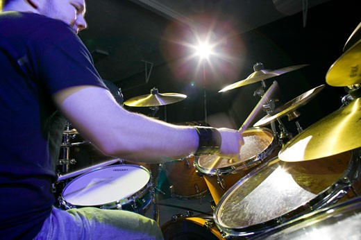 Young man playing drums on stage, portrait, low angle view : Stock Photo