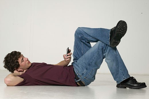 Young man using mobile phone, lying in studio : Stock Photo