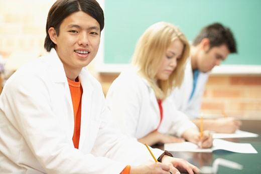 Two young men and a young woman wearing lab coats in a classroom : Stock Photo