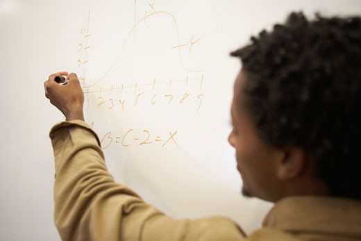 Rear view of a young man writing on a chalkboard : Stock Photo
