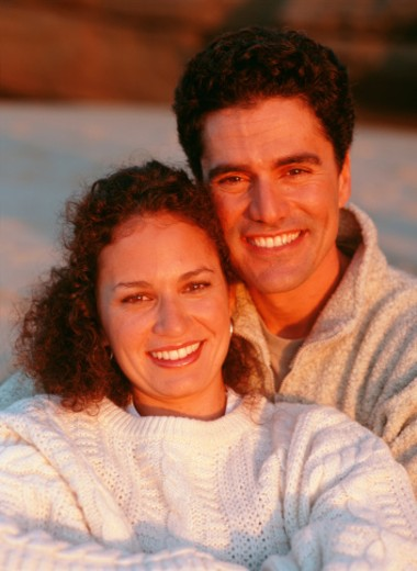Couple sitting together on beach, smiling, close-up, portrait : Stock Photo