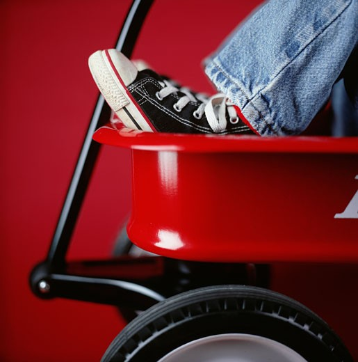 Young boy sitting in red toy carrier, close-up, low section : Stock Photo