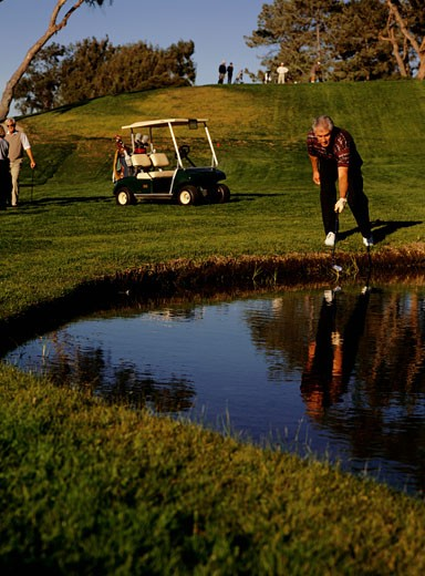 Man removing ball from pond on golf course : Stock Photo