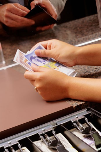Teller counting money for customer in bank, close-up of hands : Stock Photo