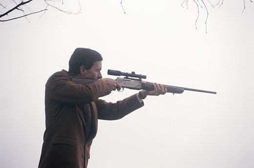 Man with shotgun aiming outdoors, low angle view : Stock Photo