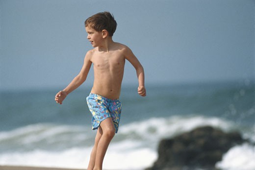 Boy (8-9) running on beach, looking over shoulder : Stock Photo