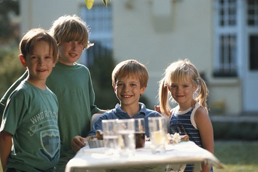 Four children (3-13) standing by dining table outdoors, portrait : Stock Photo