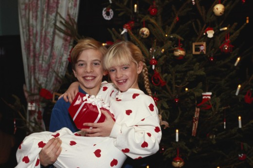 Boy (10-12) carrying girl (6-9) standing by Christmas tree : Stock Photo