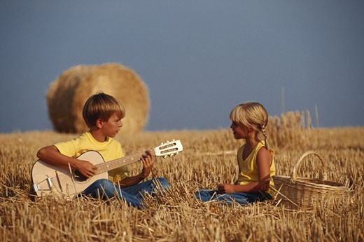 Boy and girl (4-7) sitting on hay, face to face : Stock Photo