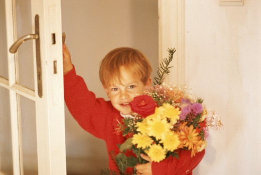 Stock Photo: 1598R-180340 Boy (4-5) at door holding bunch of flowers