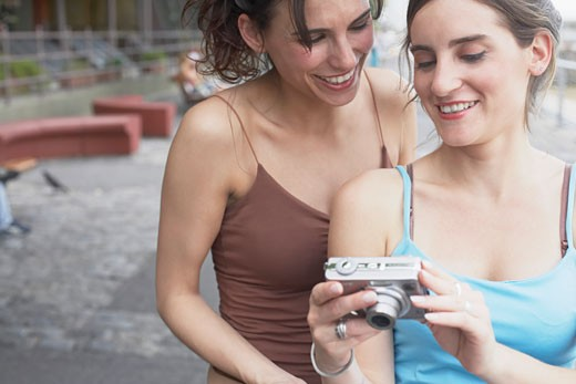 Close-up of two young women looking at a digital camera : Stock Photo
