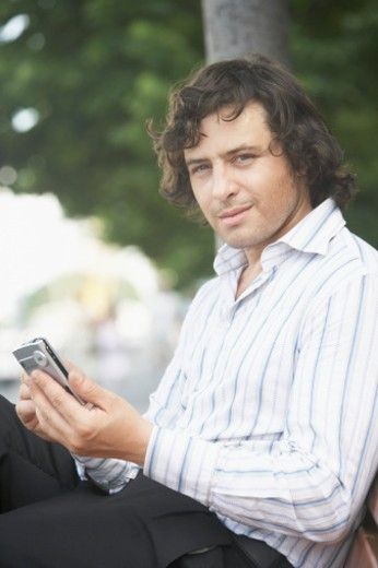 Stock Photo: 1598R-180452 Portrait of a businessman holding a hand held device