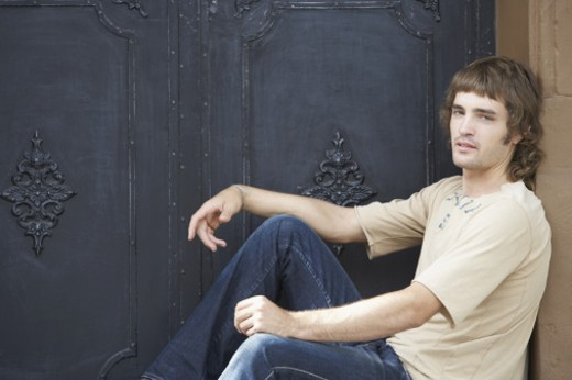 Portrait of a young man sitting in front of a door : Stock Photo