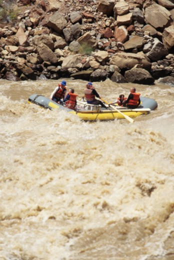 Four people river rafting in canyon : Stock Photo